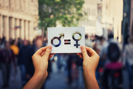 Gender equality concept as woman hands holding a white paper sheet with male and female symbol over a crowded city street background. Sex sign as a metaphor of social issue.