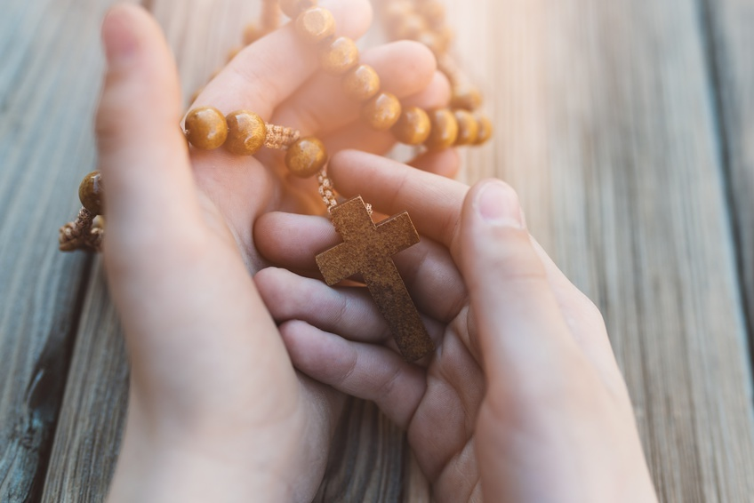 Little boy holding old wooden rosary. Child praying