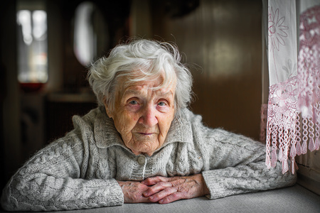 Gray-haired elderly woman sitting near the window.